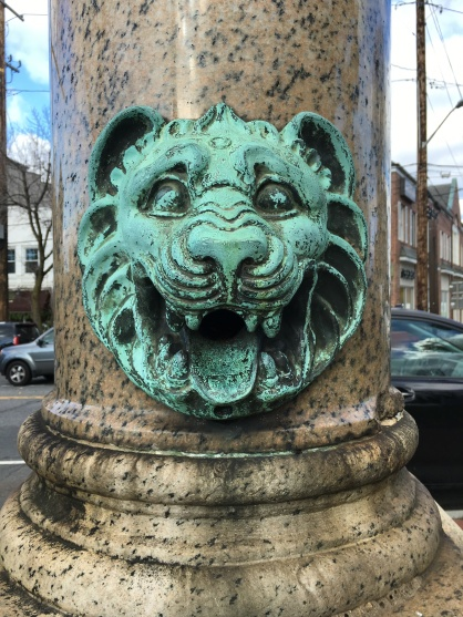 The now dry lion head spout on the south side of the monument.